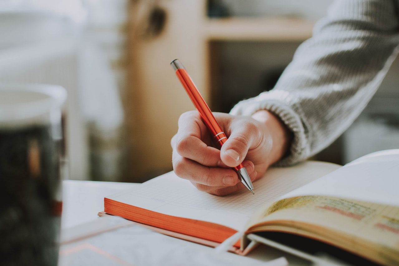 student writing with pen in notebook